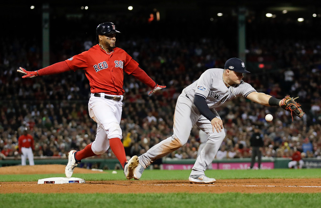 . New York Yankees first baseman Luke Voit, right, fails to hang on to the throw after a single by Boston Red Sox\'s Xander Bogaerts during the fifth inning of Game 1 of a baseball American League Division Series on Friday, Oct. 5, 2018, in Boston. (AP Photo/Charles Krupa)