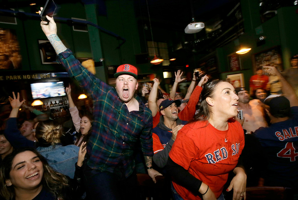 . Boston Red Sox fans celebrate while watching a televised Game 5 World Series baseball game in a bar, in Boston, Sunday, Oct. 28, 2018, moments after the Red Sox beat the Los Angeles Dodgers 5-1, in Los Angeles, to win the series 4 games to 1. (AP Photo/Steven Senne)