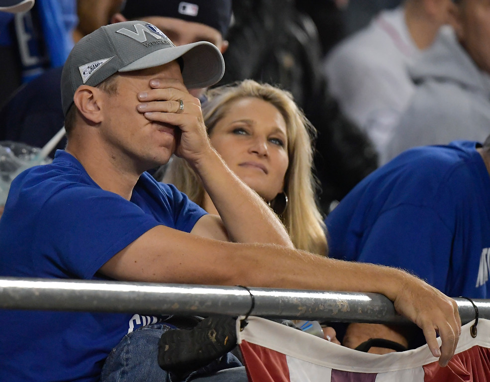 . A Los Angeles Dodgers fan wipes his face during the eighth inning in Game 5 of the World Series baseball game against the Boston Red Sox on Sunday, Oct. 28, 2018, in Los Angeles. (AP Photo/Mark J. Terrill)