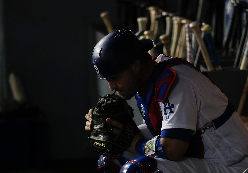 . Los Angeles Dodgers catcher Yasmani Grandal sits in dugout during the eighth inning in Game 5 of the World Series baseball game against the Boston Red Sox on Sunday, Oct. 28, 2018, in Los Angeles. (AP Photo/Jae C. Hong)