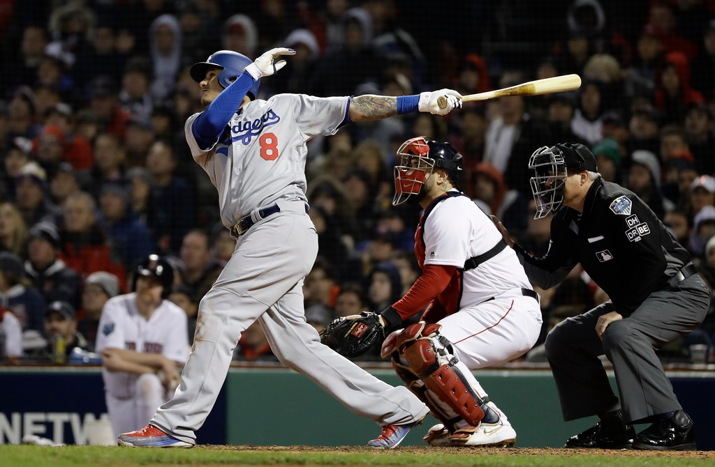 . Los Angeles Dodgers\' Manny Machado hits an RBI sacrifice fly during the seventh inning of Game 1 of the World Series baseball game against the Boston Red Sox Tuesday, Oct. 23, 2018, in Boston. (AP Photo/Matt Slocum)
