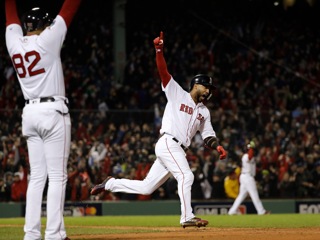 . Boston Red Sox\'s Eduardo Nunez reacts as he runs past Boston Red Sox first base coach Tom Goodwin after hitting a three-run home run during the seventh inning of Game 1 of the World Series baseball game against the Los Angeles Dodgers Tuesday, Oct. 23, 2018, in Boston. (AP Photo/David J. Phillip)
