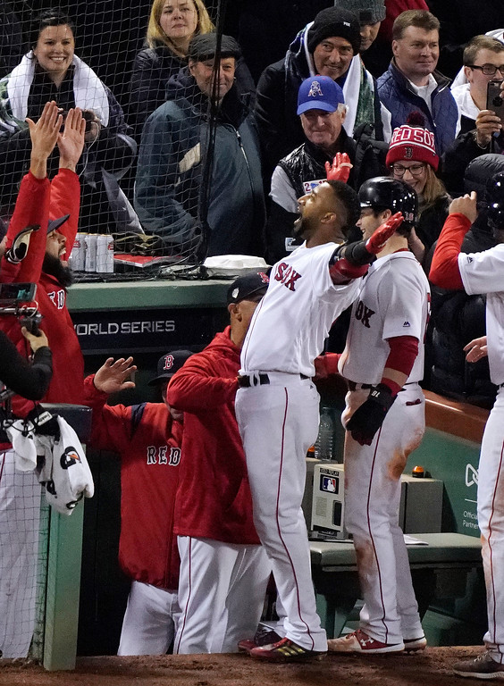 . Boston Red Sox\'s Eduardo Nunez, center, celebrates at the dugout after hitting a three-run home run against the Los Angeles Dodgers during the seventh inning of Game 1 of the World Series baseball game Tuesday, Oct. 23, 2018, in Boston. (AP Photo/Elise Amendola)