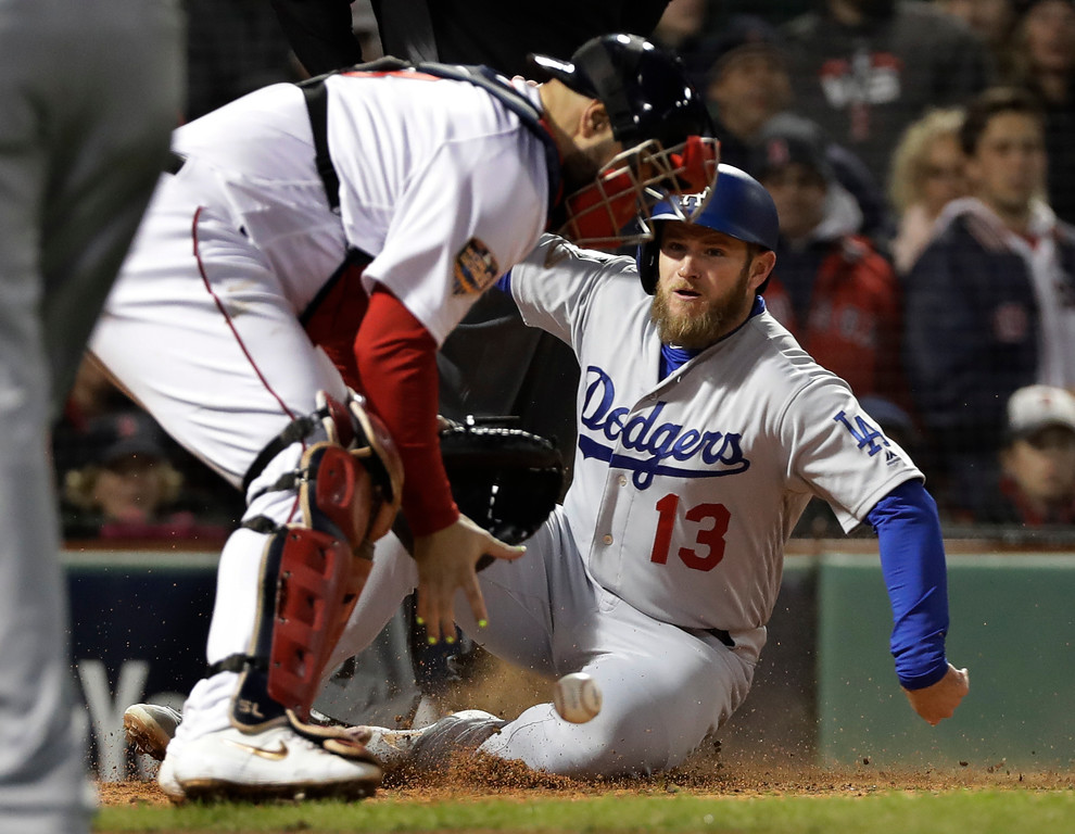 . Los Angeles Dodgers\' Max Muncy scores ahead of the throw to Boston Red Sox catcher Sandy Leon on a sacrifice fly by Los Angeles Dodgers\' Manny Machado during the seventh inning of Game 1 of the World Series baseball game Tuesday, Oct. 23, 2018, in Boston. (AP Photo/David J. Phillip)