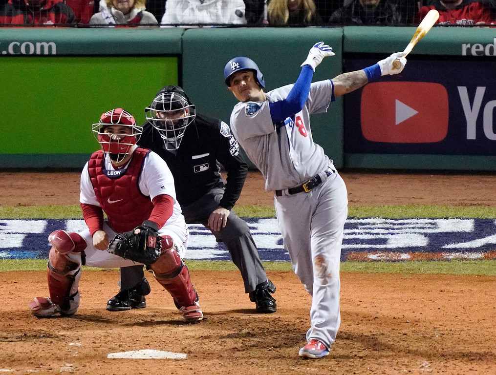 . Los Angeles Dodgers\' Manny Machado hits a sacrifice fly to drive in Max Muncy during the seventh inning of Game 1 of the World Series baseball game against the Boston Red Sox Tuesday, Oct. 23, 2018, in Boston. (AP Photo/Elise Amendola)