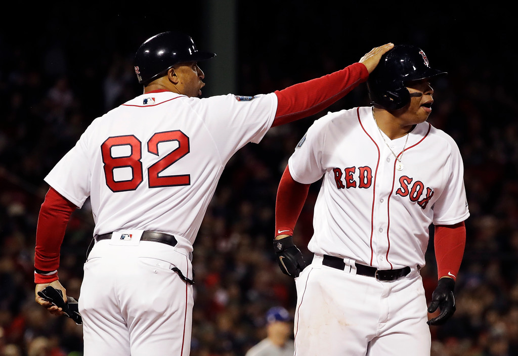 . Boston Red Sox\'s Rafael Devers is congratulated by Boston Red Sox first base coach Tom Goodwin after hitting an RBI single to score Andrew Benintendi during the fifth inning of Game 1 of the World Series baseball game Tuesday, Oct. 23, 2018, in Boston. (AP Photo/David J. Phillip)