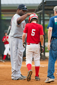 Coach Coop checking on Christopher, who was shaken up in a collision at 1st base in the bottom of the 1st inning. He didn't return to the game until the 4th inning. The Nationals finished the regular season tied for first place in the American League, but were simply no match for the Athletics tonight. Having split their regular season games, we expected a competitive playoff game, but the Athletics started their ace pitcher and came to hit, handing the Nationals a 2-14 loss. Though the Nationals were eliminated from the playoffs earlier than expected, they had a great season. CONGRATULATIONS to the Nats for taking home the AL pennant. 2012 Arlington Little League Baseball, Majors Division. (Image taken by Patrick R. Kane on 12 Jun 2012 with Canon EOS-1D Mark III at ISO 3200, f4.0, 1/640 sec and 192mm)