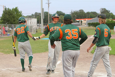 Connor Wilburn is congratulated by the team after he hits a homerun over the 335-yard left field fence in the third inning.