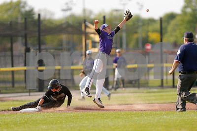 Brownsburg high school third baseman Michael Oliger  (19) jumps and streches to make the catch as Zionsville high school third baseman Chad Garisek (3) slides into third during the game between Zionsville vs Brownsburg at Brownsburg High School in Brownsburg,IN. (Jeff Brown/Flyer Photo)