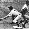 Mickey Mantle stretches for a throw to get Ray Oyler out at first