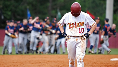 Lassiter's Brandon Stephens lowers his head as he walks off the field as North Cobb celebrate their 4-3 victory and advance to the Class AAAAA State quarterfinals.