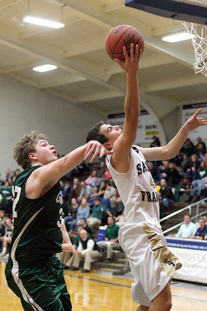 Record-Eagle/Jan-Michael Stump<br /> Traverse City St. Francis guard Ian Spencer (4) drives to the basket past Grayling forward Steven Enos (32) in the third quarter of Tuesday's game.
