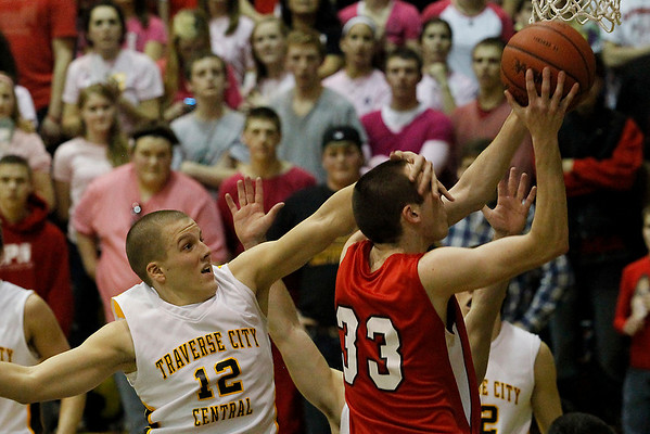 Record-Eagle/Jan-Michael Stump<br /> Suttons Bay's Stephen Wheelock (33) gets fouled during a layup by Traverse City Central's Joe Prokes (12) in the third quarter of Monday's game.