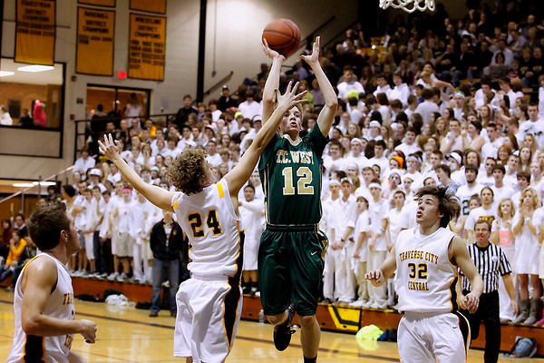 Record-Eagle/Jan-Michael Stump<br /> Traverse City West's Jeremiah Williams (12) shoots over Traverse City Central's Mark Jones (24) in the second quarter of Friday's game.