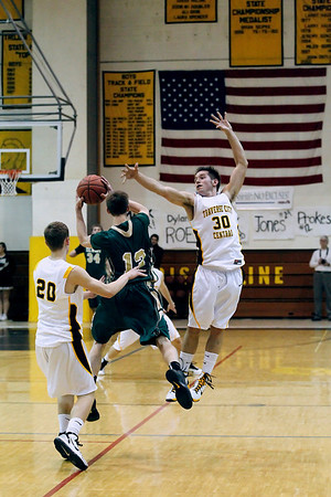 Record-Eagle/Jan-Michael Stump<br /> Traverse City West's Jeremiah Williams (12) passes between Traverse City Central's Jack Stevens (20) and Dylan Roe (30) in the first half of Frday's game.