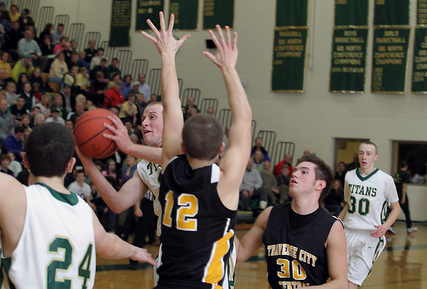 Record-Eagle/Keith King<br /> Traverse City West's Jon Oakley shoots the ball near Traverse City Central's Joe Prokes (12) and Dylan Roe (30) Thursday, January 20, 2011 at Traverse City West High School.