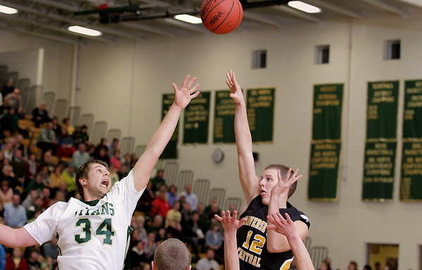 Record-Eagle/Keith King<br /> Traverse City Central's Joe Prokes, right, shoots the ball near the outstretched arm of Traverse City West's Julius Moss Thursday, January 20, 2011 at Traverse City West High School.