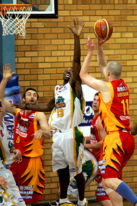 Axel Dench (wearing Neli Mottram's singlet) shoots, avoiding the reach of Larry Abney - NBL Blitz, Coffs Harbour, 8-9 September 2006