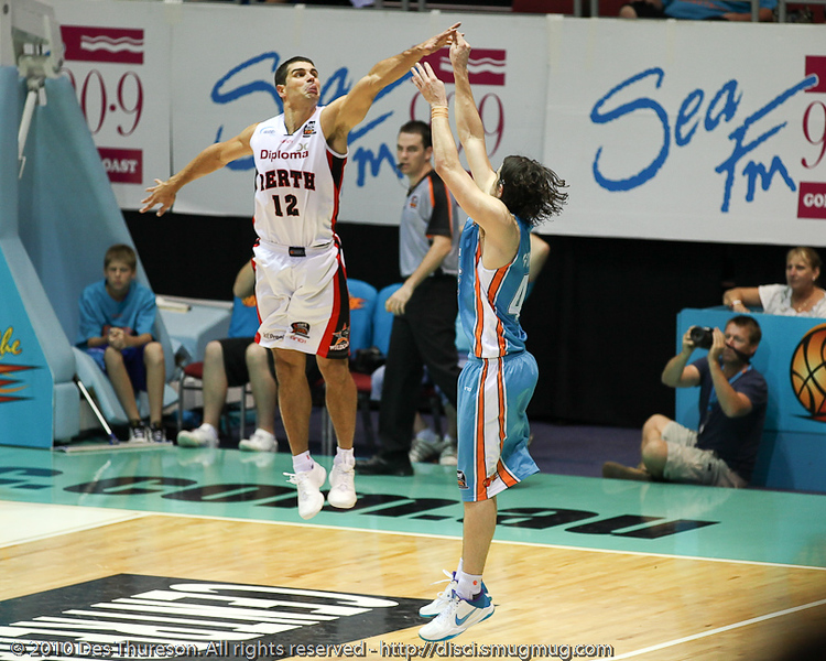 Kevin Lisch with the elevating close out on Chris Goulding - Gold Coast Blaze v Perth Wildcats NBL Baskeball, New Year's Eve 2010; Gold Coast Convention & Exhibition Centre.