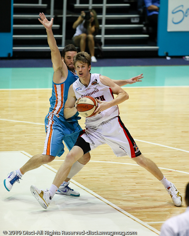 Adam Gibson keeps his hands out whilst defending Cameron Tovey - Gold Coast Blaze v Perth Wildcats NBL Baskeball, New Year's Eve 2010; Gold Coast Convention & Exhibition Centre.