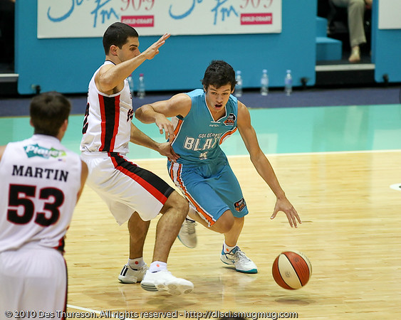 Jason Cadee drives around Kevin Lisch - Gold Coast Blaze v Perth Wildcats NBL Baskeball, New Year's Eve 2010; Gold Coast Convention & Exhibition Centre.