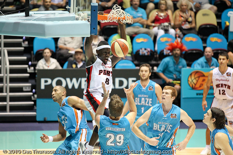 Ater Majok is surrounded by the entire blaze on-court team, but still manages the emphatic dunk - Gold Coast Blaze v Perth Wildcats NBL Baskeball, New Year's Eve 2010; Gold Coast Convention & Exhibition Centre.