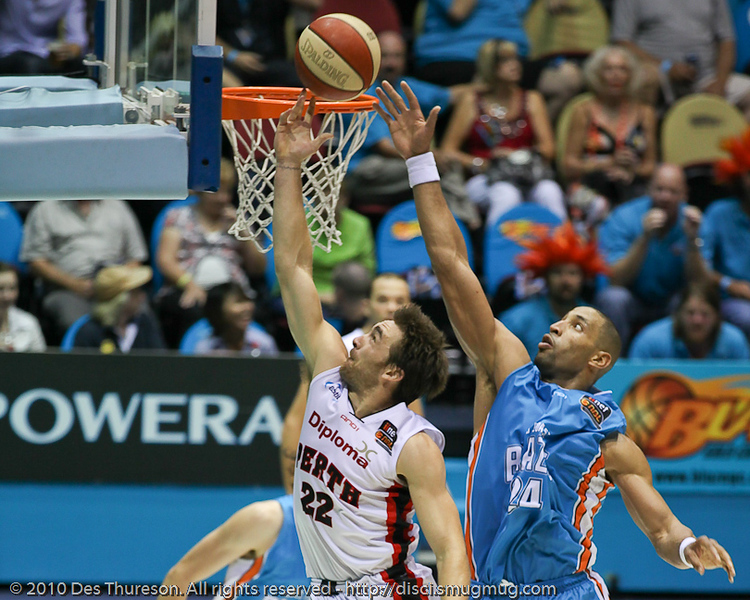 Brad Robbins takes on the tall timber of Ira Clark - Gold Coast Blaze v Perth Wildcats NBL Baskeball, New Year's Eve 2010; Gold Coast Convention & Exhibition Centre.