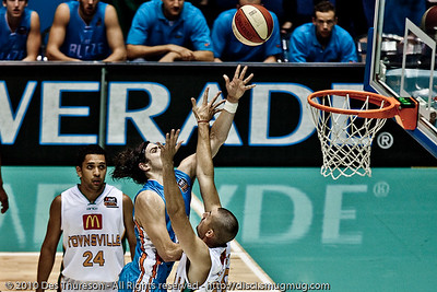 Chris Goulding drives over Russell Hinder - Gold Coast Blaze v Townsville Crocodiles NBL Basketball, Friday 17 December 2010 - National Basketball League, Gold Coast Convention & Exhibition Centre, Queensland, Australia. Photos by Des Thureson. - 'Dave Hill Temp' processing.
