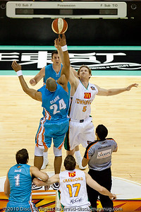 Ira Clark (GC Blaze - in blue) jumps against Luke Schenscher (Crocs - in white) - Gold Coast Blaze v Townsville Crocodiles NBL Basketball, Friday 17 December 2010 - National Basketball League, Gold Coast Convention & Exhibition Centre, Queensland, Australia. Photos by Des Thureson.