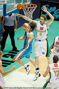 After driving from the right corner, Chris Goulding beats Luke Schenscher and makes the successful reverse bank shot - Gold Coast Blaze v Townsville Crocodiles NBL Basketball, Friday 17 December 2010 - National Basketball League, Gold Coast Convention & Exhibition Centre, Queensland, Australia. Photos by Des Thureson.