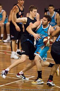 Adam Gibson drives against Tom Abercrombie - Gold Coast Blaze v New Zealand Breakers NBL basketball pre-season game; 4 October 2010, Carrara Stadium, Gold Coast, Queensland, Australia