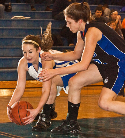 Hilliard Davidson High School's #30 Samantha Bradway tries to snag a loose ball from Central Crossings High School's #13 Olivia Davis in the first period of play at Hilliard Davidson High School Friday night January 29, 2010. (Photo by James D. DeCamp 614-462-8027)