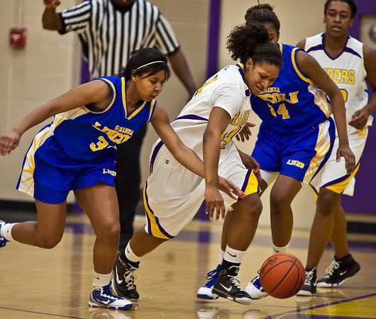 Reynoldsburg High School's #44 T'Shera Lucas tries to get away from Gahanna Jefferson High School's #33 Phylicia Marrow, left, and #34 Zenobia Bess, right, in the second period of play at Reynoldsburg High School Friday night February 12, 2010. (Photo by James D. DeCamp 614-462-8027)