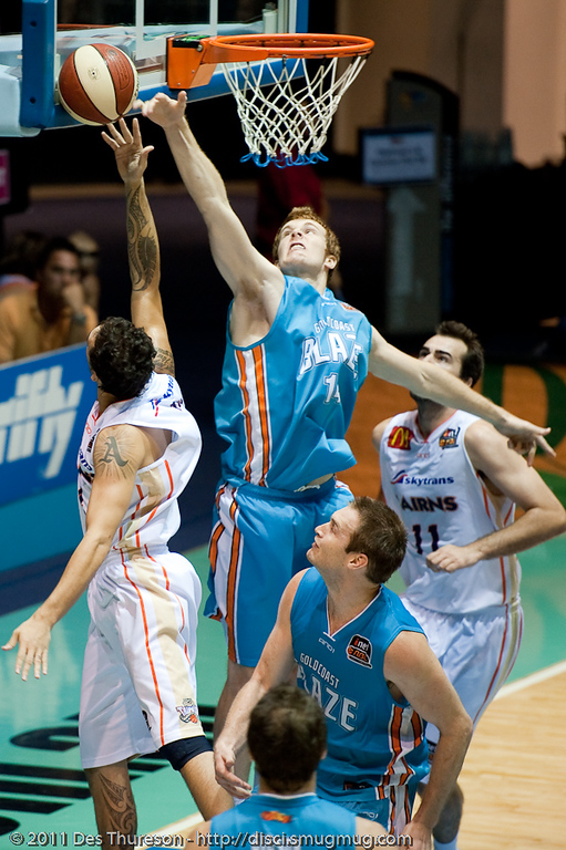 """Tom Garlepp literally gets a finger tip to Lindsay Tait's shot - Gold Coast Blaze v Cairns Taipans NBL Basketball, Wednesday 19 January 2011; Gold Coast Convention & Exhibition Centre, Broadbeach, Queensland, Australia. Photos by Des Thureson:  <a href=""""http://disci.smugmug.com"""">http://disci.smugmug.com</a>"""
