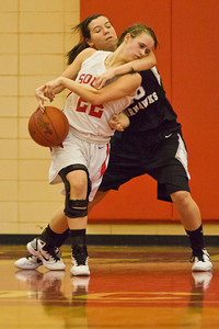 Westerville South High School's Lindsay Gerhart (22) and Westerville Central High School's Megan Mills (23) wrestle for the ball in the second period of play at Westerville South High School Saturday night January 22, 2011.
