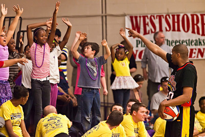 """Harlem Wizards Dwayne """"Swoop"""" Simpson (000), right, gets the kids riled up before the second half of their game against the Reynoldsburg-Pickerington Community All-Stars at the Reynoldsburg High School gymnasium Thursday evening April 14, 2011.  The game was presented by the Reynoldsburg-Pickerington Rotary Club as a fund raiser. (© James D. DeCamp 