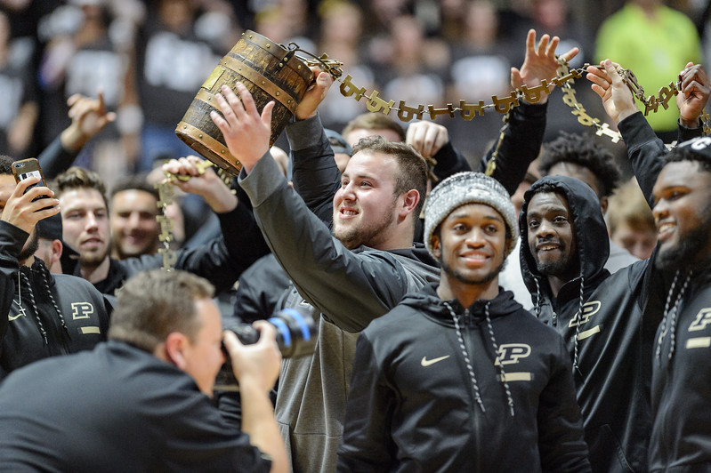 The Purdue Football team brings the Old Oaken Bucket to Mackey Arena before the start of the game.