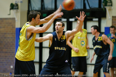 Mattie Nielsen passes under the watchful eye of David Stiff - Boomers' Basketball - Public Pre-Olympic  Training Session, 29 May 2004; Gold Coast, Queensland, Australia.