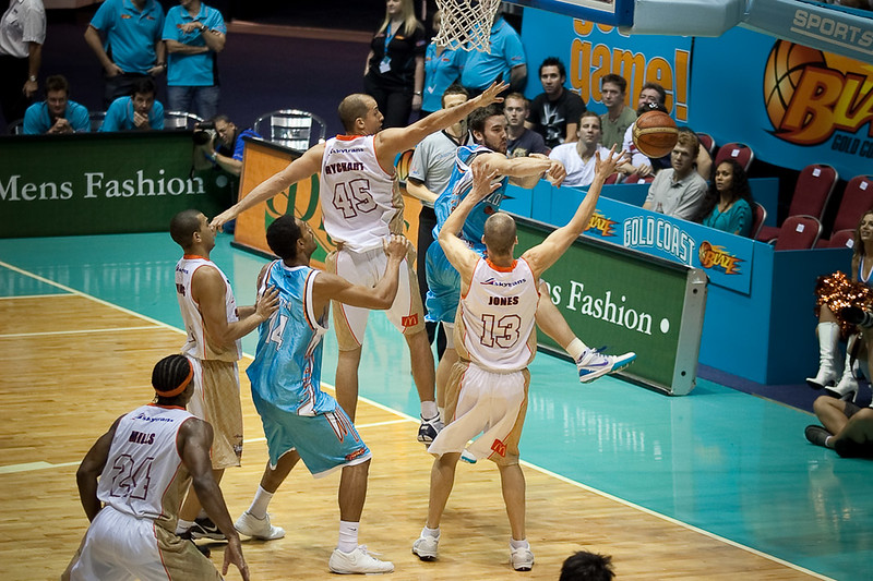 Adam Gibson dumps along the baseline while closed off by Dusty Rychart and Phill Jones - Gold Coast Blaze v Cairns Taipans, 4 December 2009.