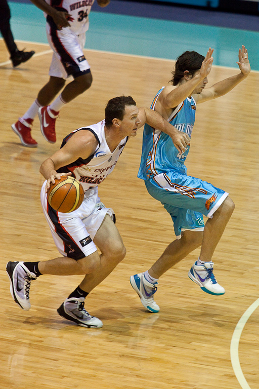 Chris Goulding practises his lotus position while defending Wildcats veteran Martin Cattalini - Gold Coast Blaze v Perth Wildcats NBL Basketball; 5 February 2010.