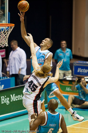Craig Bradshaw elevates strongly over giant Luke Schenscher & receives the foul - Gold Coast Blaze v Perth Wildcats Semi-final G2, 23 February 2010. After being down for most of the game, the Wildcats came back in the final minutes to score an 82-78 win. Wildcat import Kevin Lisch scored 11 of his 18 points in the final five minutes to help his team to the win.