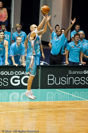 Blaze captain James Harvey shoots the 3-pointer, as injured team mate Ayinde Ubaka wishes the ball in - Gold Coast Blaze v Perth Wildcats Semi-final G2, 23 February 2010. After being down for most of the game, the Wildcats came back in the final minutes to score an 82-78 win. Wildcat import Kevin Lisch scored 11 of his 18 points in the final five minutes to help his team to the win.
