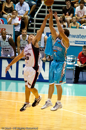 Adam Gibson just gets the shot away over Damian Martin - Gold Coast Blaze v Perth Wildcats Semi-final G2, 23 February 2010. After being down for most of the game, the Wildcats came back in the final minutes to score an 82-78 win. Wildcat import Kevin Lisch scored 11 of his 18 points in the final five minutes to help his team to the win.