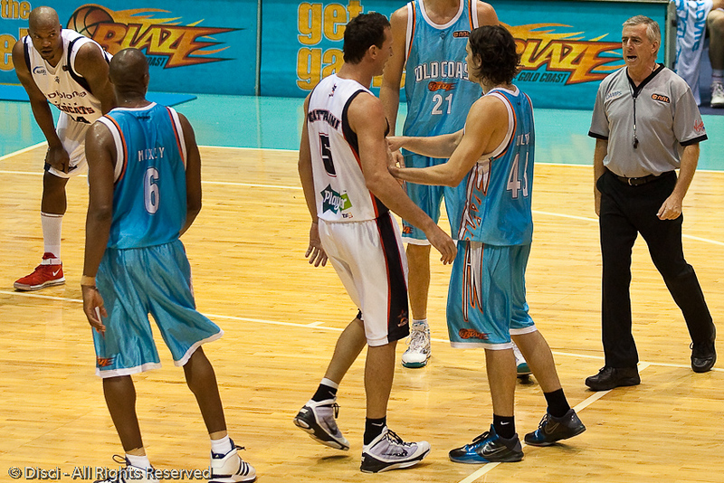 Martin Cattalini continues his trash talk with Chris Goulding after Goulding missed the first free throw. Veteran referee Roger Shields steps in to tell Cattalini to 'cool it'. - Gold Coast Blaze v Perth Wildcats Semi-final G2, 23 February 2010. After being down for most of the game, the Wildcats came back in the final minutes to score an 82-78 win. Wildcat import Kevin Lisch scored 11 of his 18 points in the final five minutes to help his team to the win.