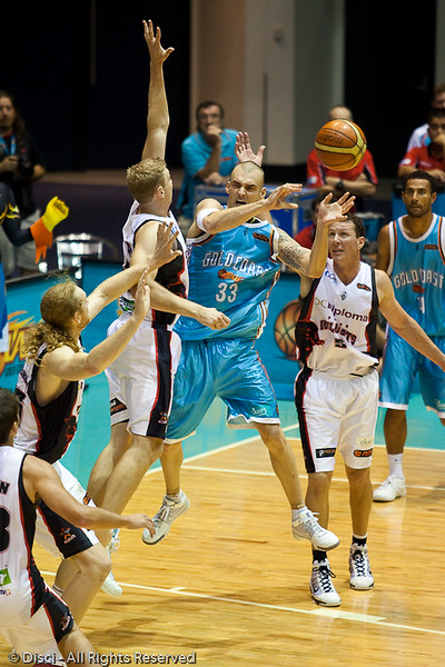 James Harvey passes whilst under pressure from Shawn Redhage - Gold Coast Blaze v Perth Wildcats Semi-final G2, 23 February 2010. After being down for most of the game, the Wildcats came back in the final minutes to score an 82-78 win. Wildcat import Kevin Lisch scored 11 of his 18 points in the final five minutes to help his team to the win.