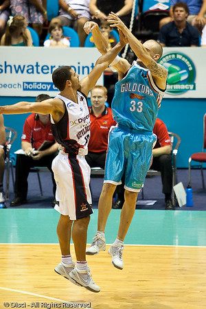 James Harvey is fouled on the arm by Kevin Lisch as Harvey takes the 3 point shot - Gold Coast Blaze v Perth Wildcats Semi-final G2, 23 February 2010. After being down for most of the game, the Wildcats came back in the final minutes to score an 82-78 win. Wildcat import Kevin Lisch scored 11 of his 18 points in the final five minutes to help his team to the win.