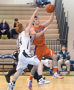 Midd-West's Elijah Fisher tries to block the layup from Danvill'es Zach Zozick during Wednesday night's game in Middleburg.
