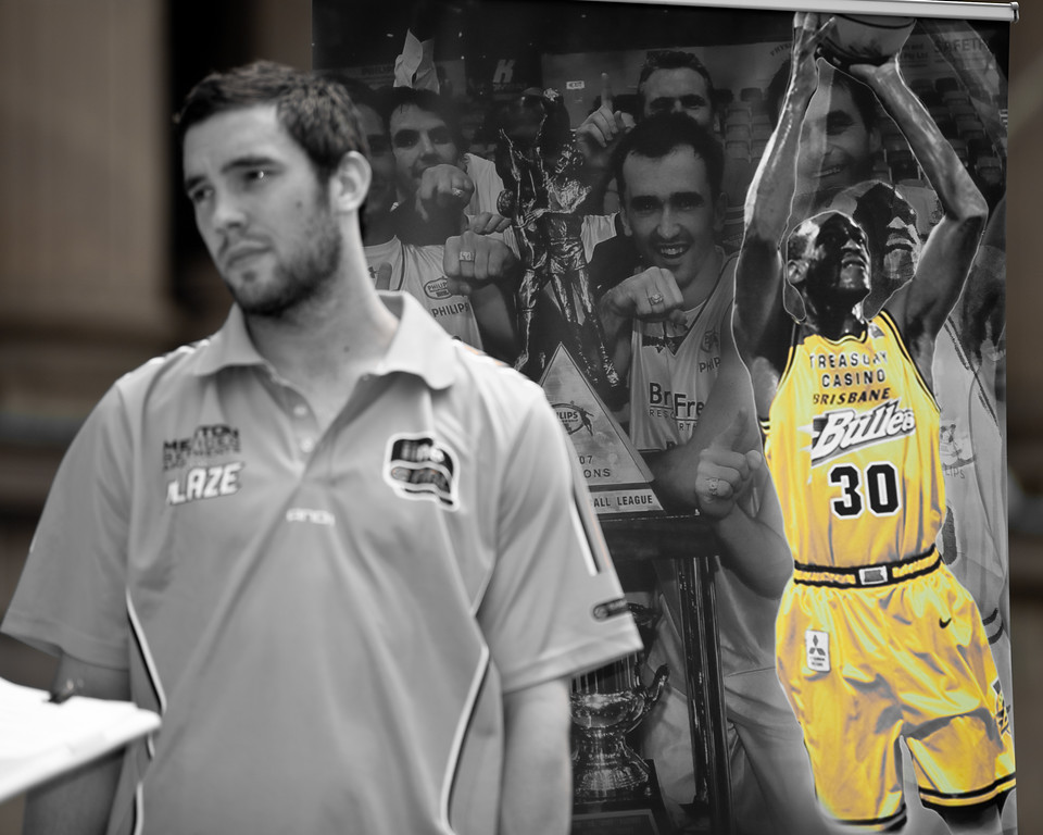 """Adam Gibson reflects on being a Brisbane Bullets Championship player (Gibbo was a member of the team pictured in the poster behind the image of Leroy Loggins.) - Bring Back the Bullets Promotion, King George Square, Brisbane, Queensland. Photos by Des Thureson:  <a href=""""http://disci.smugmug.com"""">http://disci.smugmug.com</a>."""
