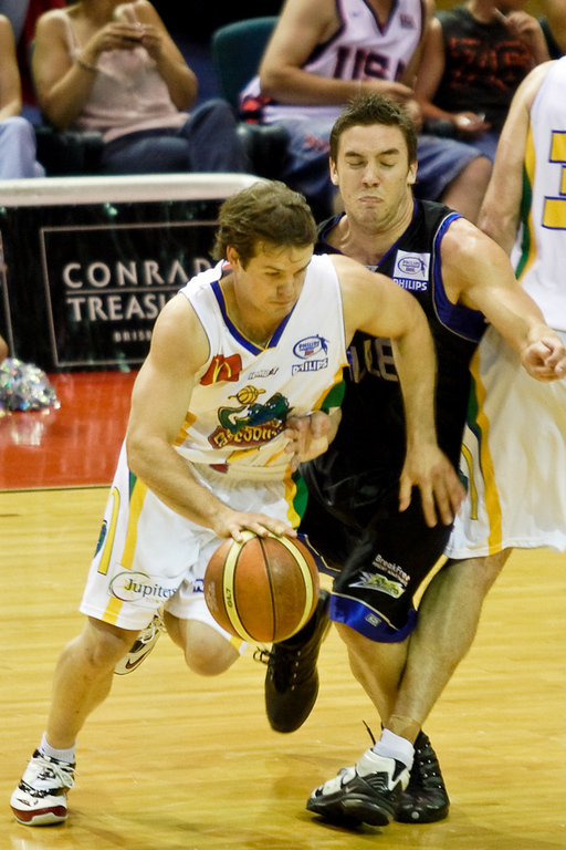 Adam Gibson gets squeezed into the screen while trying to defend Kelvin Robertson - Brisbane Bullets v Townsville Crocs 23 December 2005