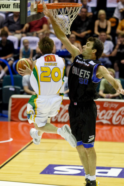 Brad Newley hangs in the air with the reverse layup against Mark Bradtke - Brisbane Bullets v Townsville Crocs 23 December 2005